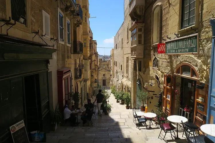 Eine schmale Gasse führt über Treppen zum Meer in Maltas Hauptstadt Valletta hinunter. Auf der linken und rechten Seite der Gasse befinden sich kleine Restaurants.
