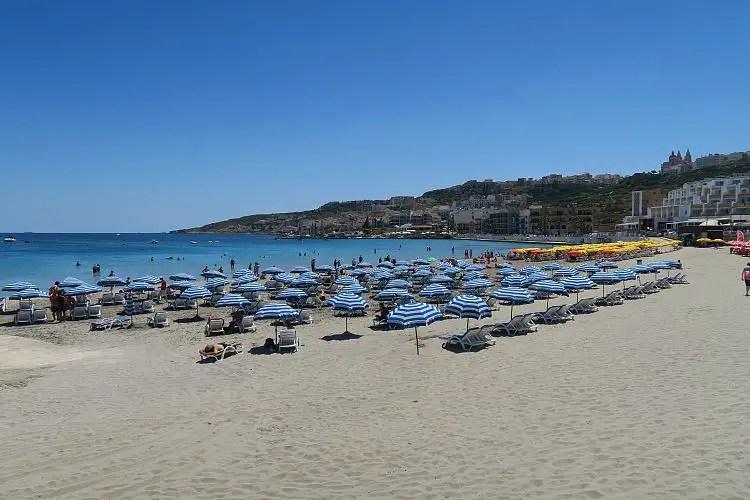 Das sonnige Wetter am Sandtrand von Melliha mit dem türkisblauen Meer, Liegestühlen und Sonnenschirmen im Norden von Malta.