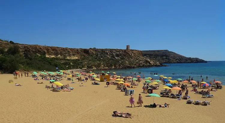 Ein breiter Sandstrand mit Sonnenschirmen und Sonnenliegen am türkisblauen Meer.