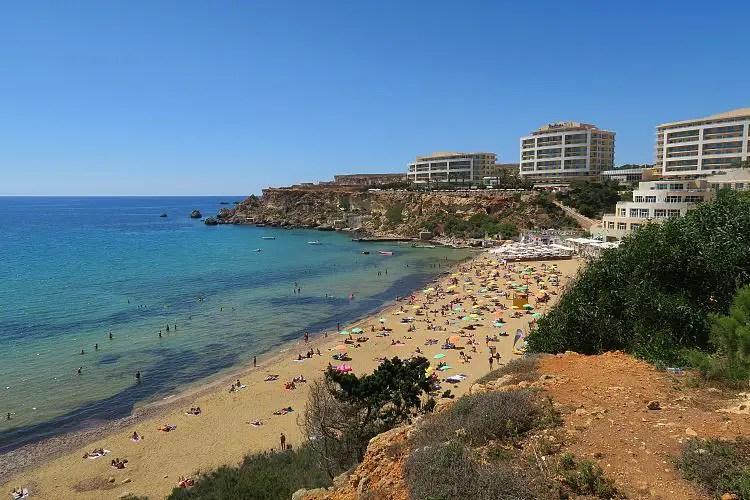 Der Blick von den Klippen auf den Sandstrand in der Golden Bay, das Golden Sands Hotel und das türkisblaue Meer.