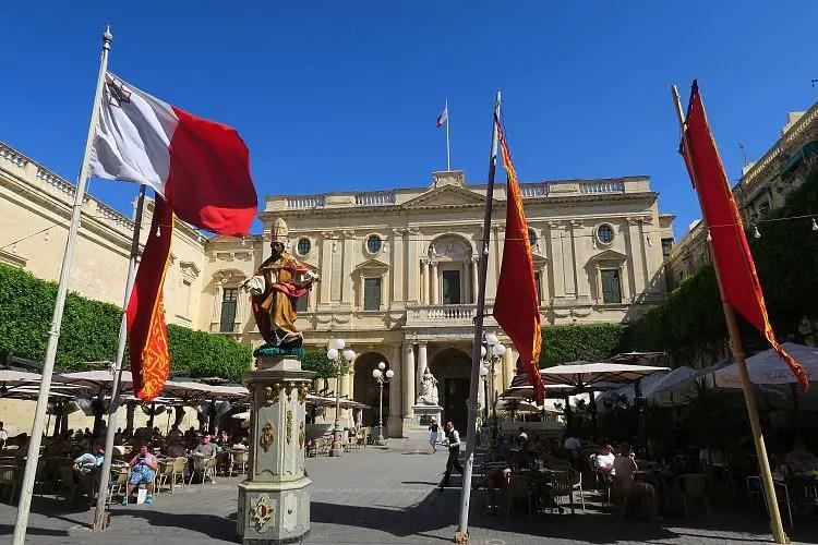 Der Platz vor der Nationalbibliothek von Malta mit einem Gastgarten und maltesischen Flaggen.