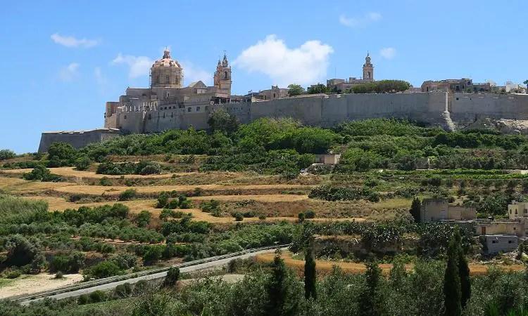 Die Straße zwischen den Feldern unterhalb der mittelalterlichen Festung Mdina auf Malta.