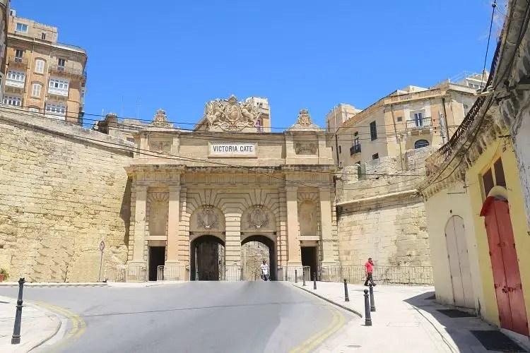 Der Blick vom Hafen auf das aus drei Torbögen bestehende, weiße Victoria Gate und die Stadtmauern.
