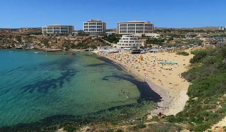 Das türkisblaue Meer am Golden Bay Sandstrand und das dahinterliegende Radisson Blu Resort Hotel.