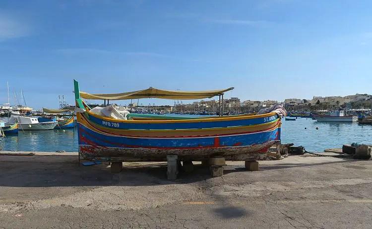 Ein rot-gelb-blaues Luzzu Boot steht am Land, neben dem Fischereihafen von Marsaxlokk.
