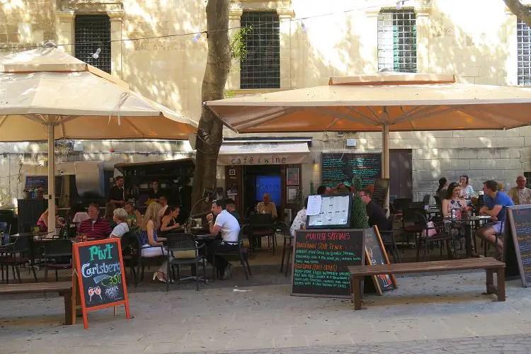 Der Gastgarten eines mit Sonnenschirmen überdachten Restaurants.