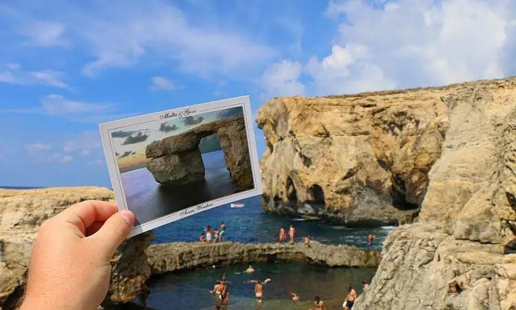 Eine Hand hält eine Postkarte mit dem Azure Window an die Stelle am Meer an dem es eingestürzt ist.