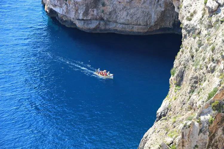 Kleines Boot unter dem natürlichen Felsbogen an der Blauen Grotte.