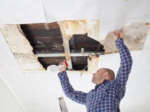 man cleaning water damage on his ceiling
