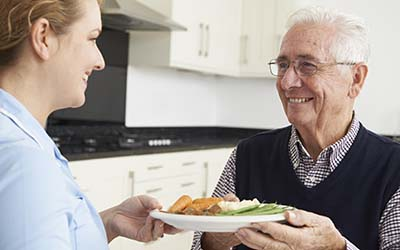 image of caregiver giving senior a prepared meal