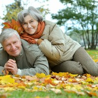 senior couple playing in the fall leaves