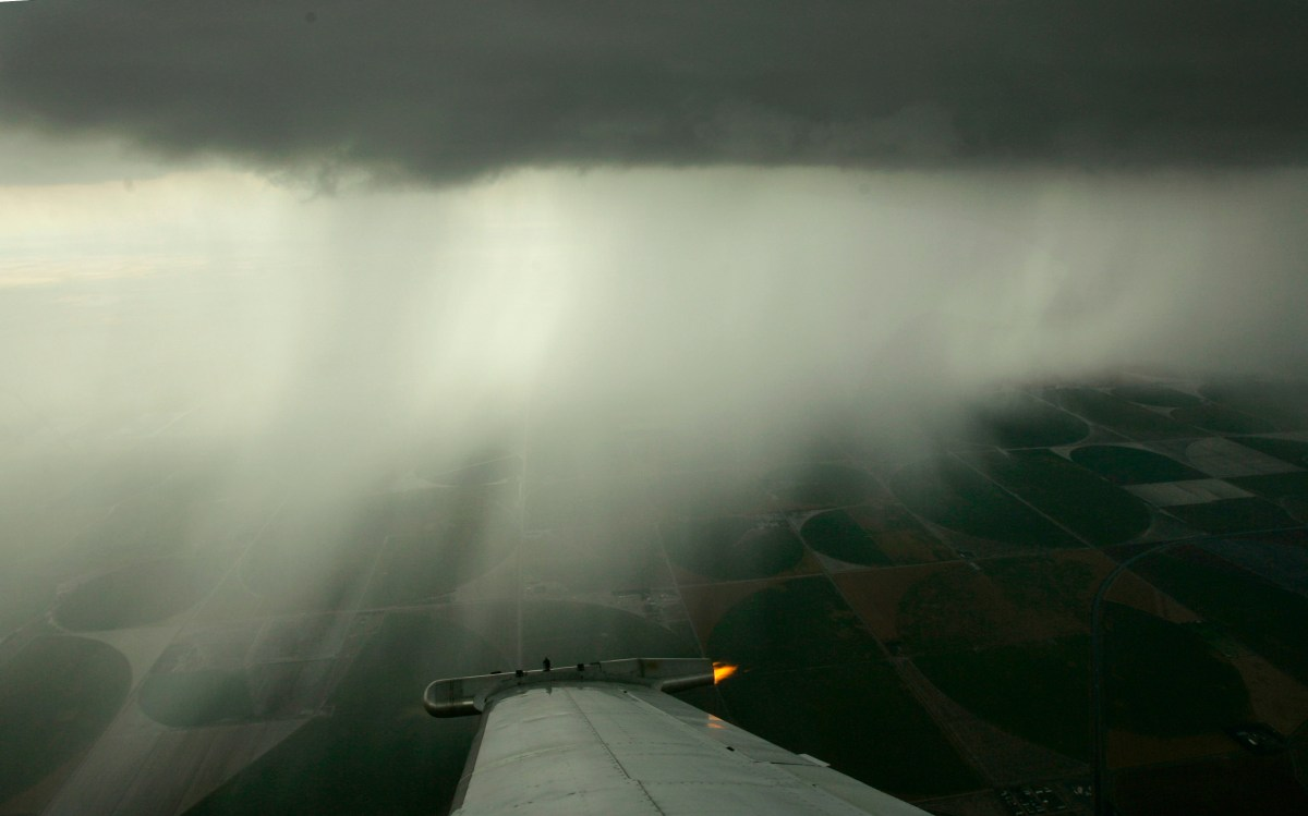 A wing-mounted generator emits particles of silver iodide as part of a cloud seeding mission run by the Western Kansas Weather Modification program. The program aims to reduce crop damage from hail by saturating storm clouds with silver iodide particles. Photo: Charlie Riedel / AP