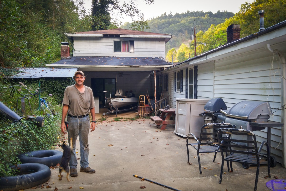 Elvis Thacker stands on his home's back patio that was covered by more than a foot and a half of mud. Photo: Benny Becker / Ohio Valley Resource