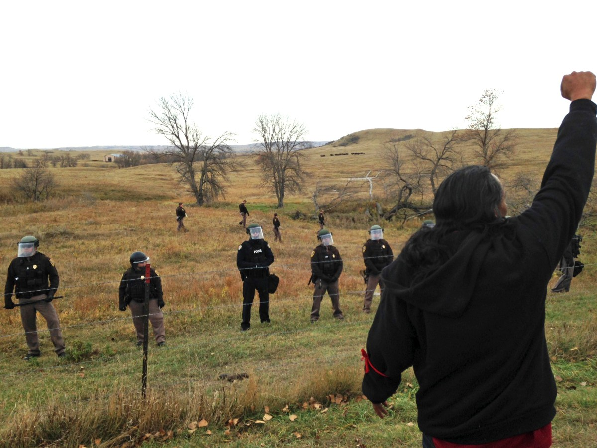 A Dakota Access pipeline protester defies law enforcement officers who are trying to force them from a camp on private land in the path of pipeline construction, Thursday, Oct. 27, 2016. Soldiers and law enforcement officers dressed in riot gear began arresting protesters who had set up a camp on private land to block construction of the Dakota Access oil pipeline. Photo: James MacPherson