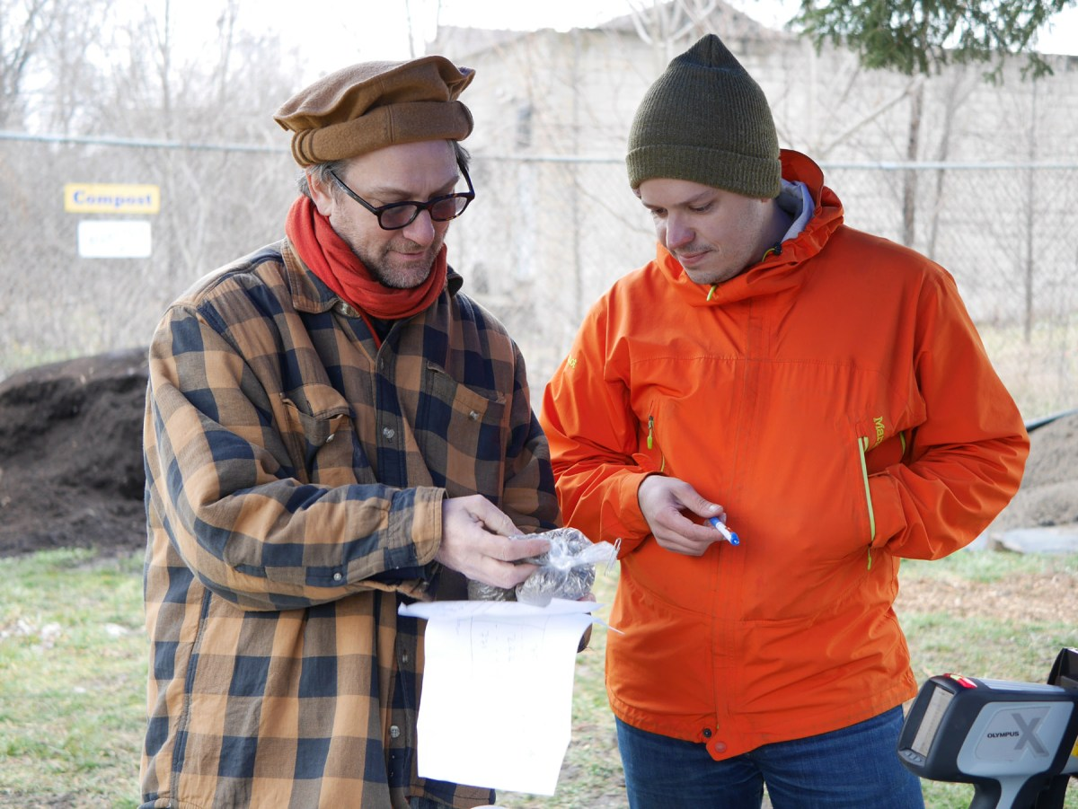 Hydrologist Ian Lipsky and Jonathan Burgess (right), Senior Agricultural Conservationist with Allegheny County Conservation District, look over a soil sample at a free lead screening in Pittsburgh's Larimer neighborhood. Photo: Kara Holsopple