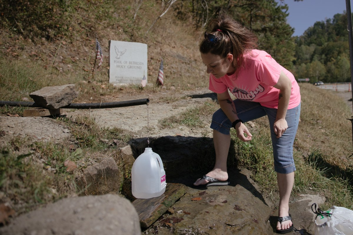 BarbiAnn Maynard drives 45 minutes from her home in Martin County, Kentucky, to a spring at the Mingo-Logan county line in West Virginia to fill containers with fresh water. Like most of her neighbors, Maynard doesn't trust the water in Martin County, which routinely exceeds maximum levels of contaminants, including the carcinogen trihalomethane. (Photo by Curren Sheldon/100 Days in Appalachia)