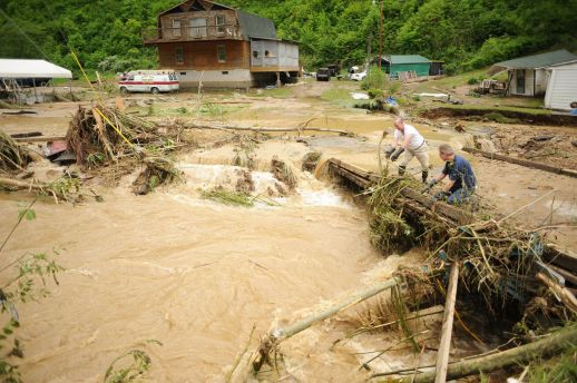 Two men work to clear debris from a bridge in Varney, West Virginia, after Pigeon Creek and others in the area badly flooded homes and businesses in Mingo County in May 2009. File Photo: Logan Banner