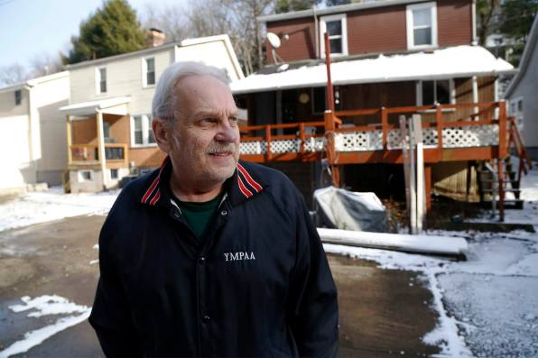 Anthony Wolkiewicz photographed behind his house on Provost Road in the flood-prone Overbrook neighborhood of Pittsburgh. (Photo by Ryan Loew/PublicSource)