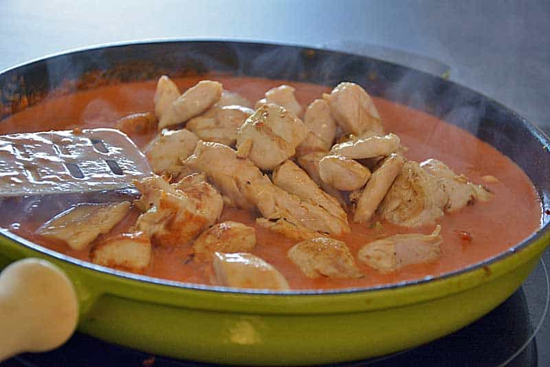 Einfaches Hühnercurry wird in einer großen Pfanne zubereitet