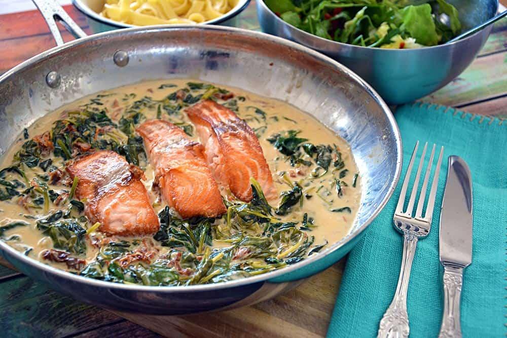 Das Gericht Lachs in Sahne mit Spinat ist ein einfaches Mittagessen oder Abendessen. Es wird in der Pfannne gebraten und braucht nicht in den Ofen. Dazu gibt es Nudeln und Salat.