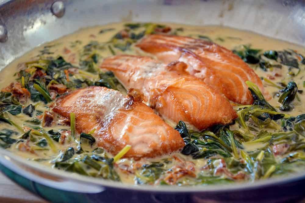 Das Rezept für Lachs in Sahne mit Spinat ist herrlich herzhaft, einfach und schmeckt der ganzen Familie. Es wird in der Pfanne gebraten.