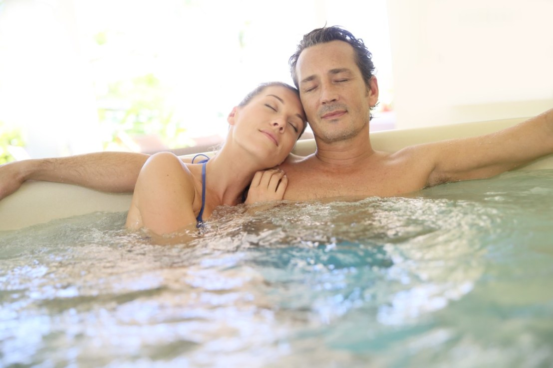 Romantic couple relaxing with eyes shut in jacuzzi