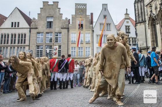 """Die erdfarbenen """"Creatures"""" zogen mitten durch die farbentragenden Burschenschaftler vor der Lambertikirche. (Foto: Thomas Hölscher)"""