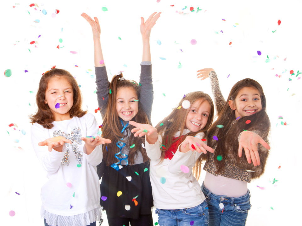 4 girls smiling at camera with feathers and glitter thrown in the air