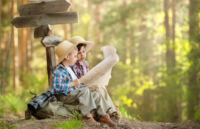 Two boys reading maps in forest
