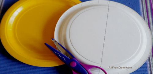 two yellow paper plates with one marked for cutting in half