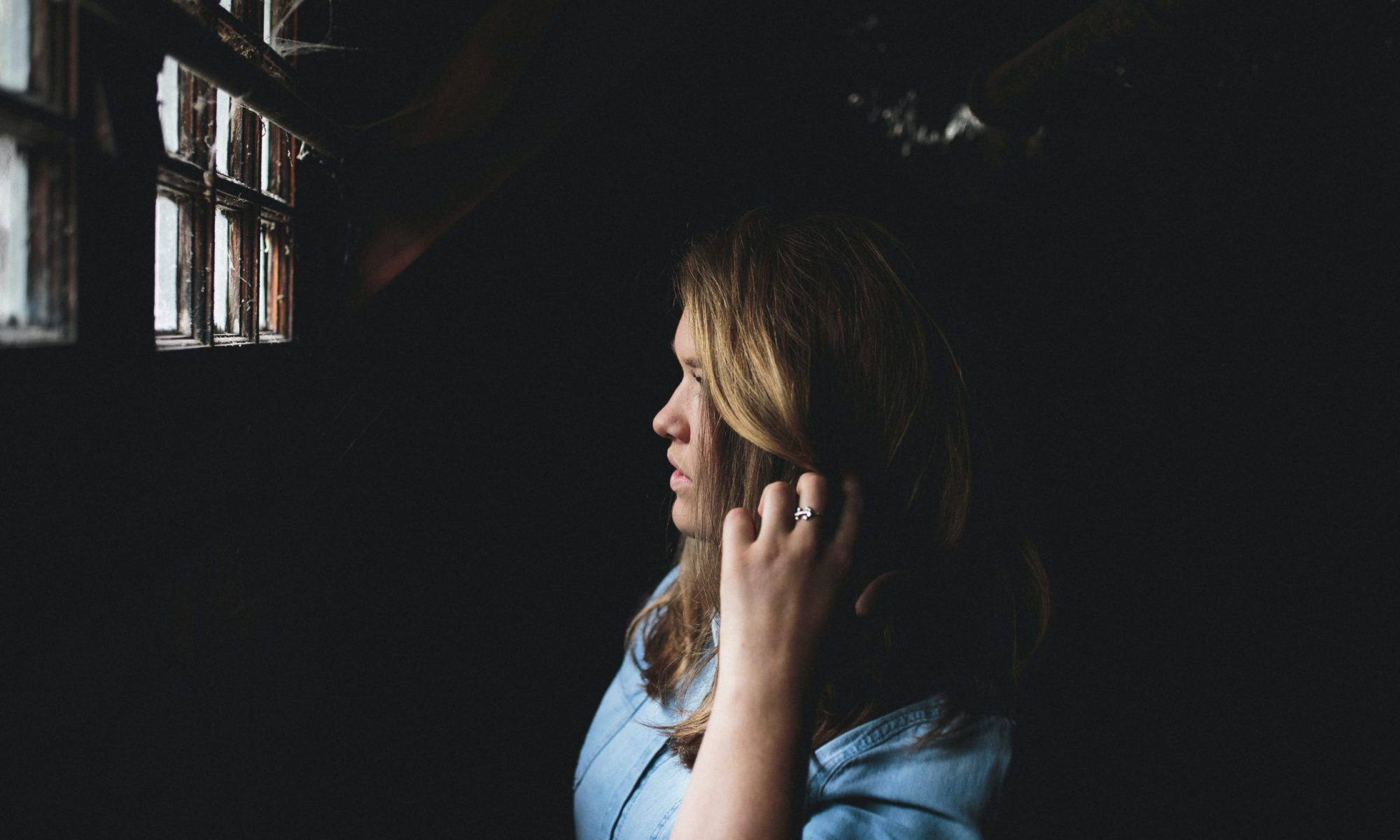 woman in a dark room overcoming imposter syndrome