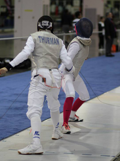two women fencing, one with the name Thurman on the back of her uniform