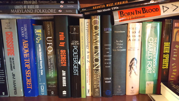 shelf of books with titles about UFOs, poltergeists, hidden animals, conspiracies