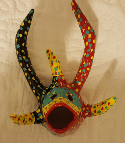 Small black, green, yellow, and red mask with pointed open mouth and five horns