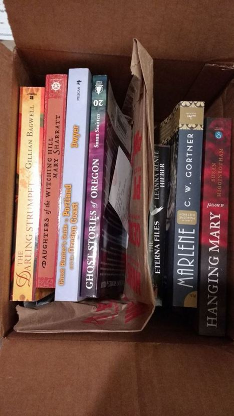 Stack of books; Bagwell's The Darling Strumpet, Sharratt's Daughters of the Witching Hill, Dwyer's Ghost Hunter's Guide to Portland and the Oregon Coast, Smiten's Ghost Stories of Oregon, Hieber's The Eterna Files, Gortner's Marlene, and Higganbotham's Hanging Mary