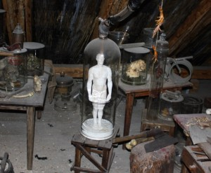 photo of small plaster figure under glass, surrounded by alchemical apparatus and tools