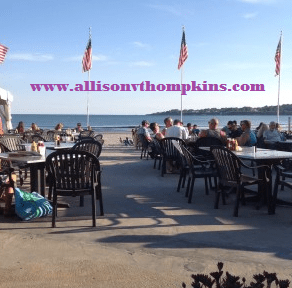 Image of people eating dinner on an outdoor patio with beach and ocean beyond the patio.