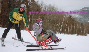 Photo: Male ski instructor wearing green and yellow coat, black pants, and red skis is standing behind woman who is seated in a sit ski and wearing a purple and gray coat, gray blanket and purple pants. They are at the top of a ski trail.