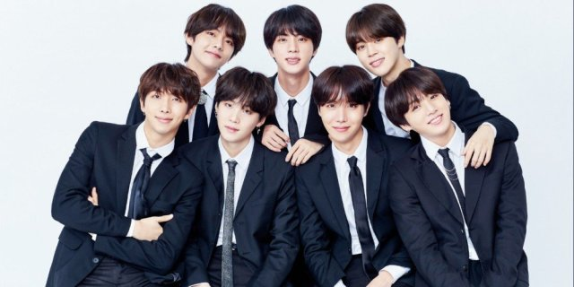 [Image Description: BTS posing for a group photoshoot wearing black formal suits and ties. Top row: V, Jin, Jimin Bottom Row: RM, Suga, J-Hope, Jungkook Source: AllKPop]