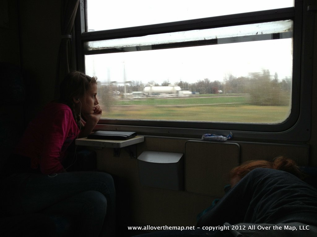 One girl looking out the train window at the Romanian landscape, another trying to get a few last moments of sleep on our Eurail with kids adventure