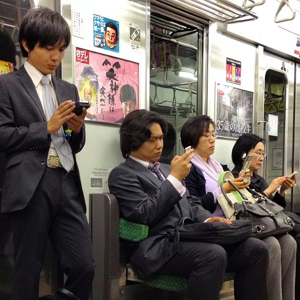 The very quiet Tokyo subway, with businessmen in suits checking their smartphones.