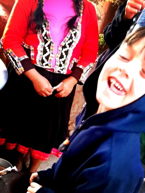 Child laughing at Awana Kancha,Peru
