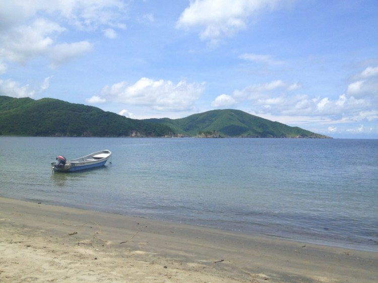 A beautiful beach and a fishing boat at Parque Tayrona