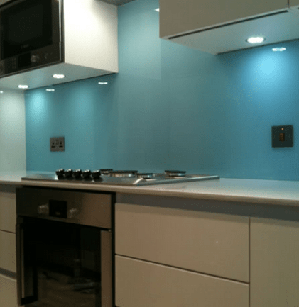 Blue back painted toughen splashback in northern ireland with glass cut outs for plugs