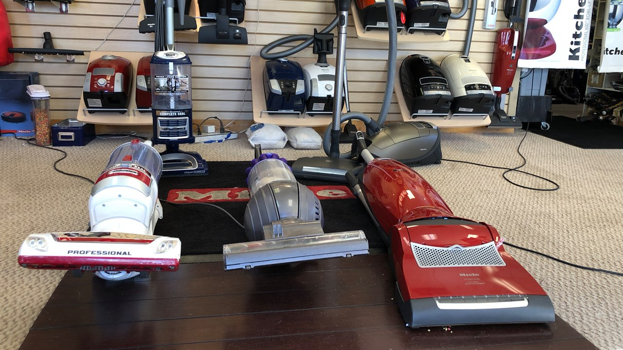 Shar vacuum next to a Dyson bagless vacuum and a Miele upright vacuum cleaner