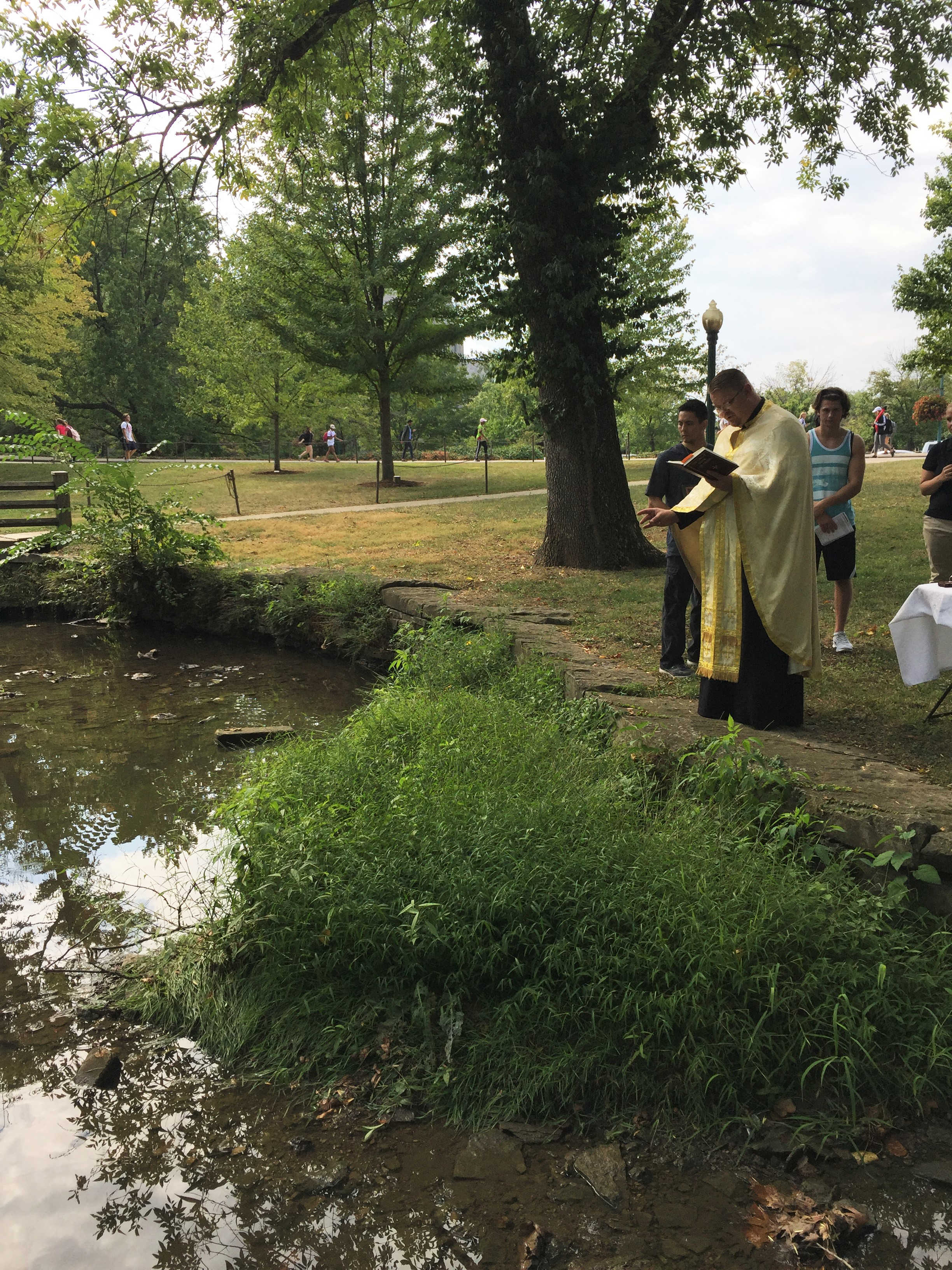 Father blesses the water which flows through campus