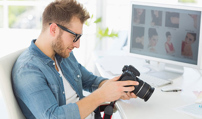 Male photographer looking at his camera in front of a computer.