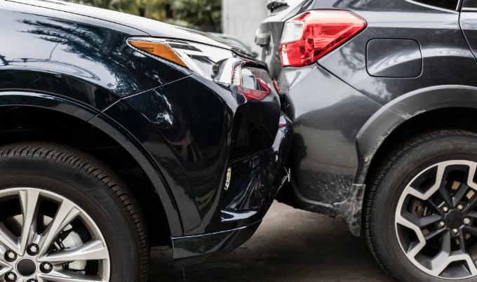 black and gray cars with dented bumpers after accident.