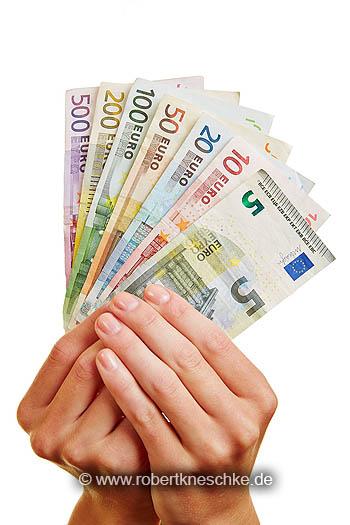 Zwei Hände halten einen Fächer aus Geldscheinen in Euro
