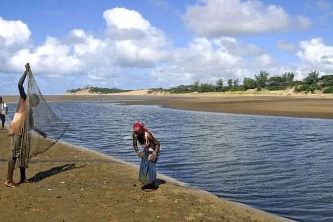 Um pescador lança a rede na praia do Zongoene